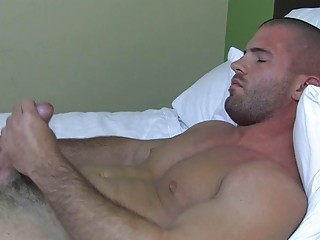 Sexy muscled delighted stud plays with his hard bazooka in bed